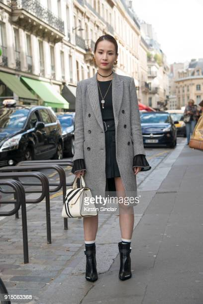 Director of Merchandising Tracey Cheng wears a Uniqlo coat Alexander Wang top Acne skirt Valextra bag and OffWhite boots day 5 of Paris Womens...