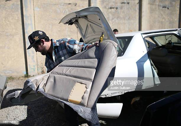 R3DNA director of operations David MillerHershon removes a leather seat from a car at a PicknPull salvage yard on October 14 2013 in Oakland...