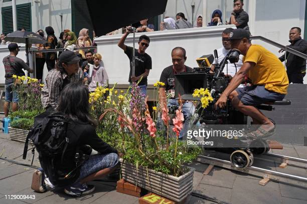 Director of photography Edi Santoso right and members of the crew use a camera dolly mounted on a track during the production of the film Sin in...
