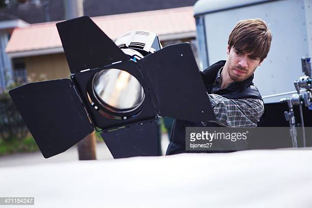 director of photography setting light - grip film crew stock photos and pictures