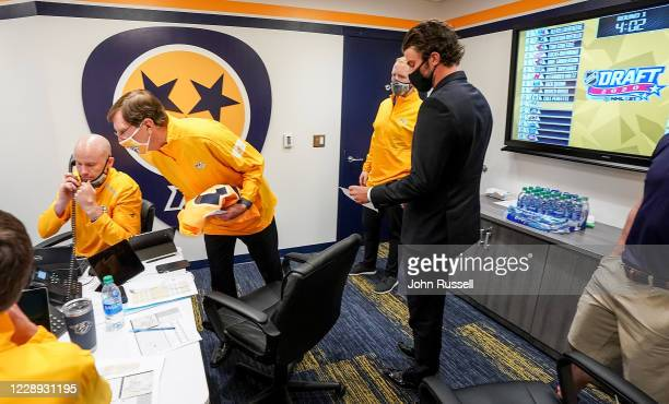 Director of Player Personnel Jeff Kealty makes a call as GM David Poile and team captain Roman Josi prepare to announce goalie Yaroslav Askarov as...