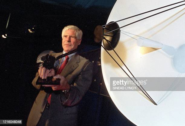 Director of Science Prof Roger Bonnet holds up a miniature model of the 'Rosetta orbiter' whilst standing next to the antenna of a bigger model of...