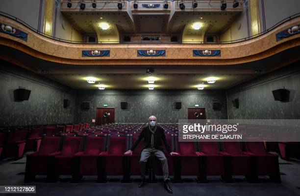Director of the Cinema Louxor Emmanuel Papillon poses with a protective facemask inside of the movie theatre on May 7 2020 in Paris as the country is...