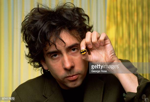 Director of the first Batman movie and Batman Returns Tim Burton proudly displays a Batman pin during a 1989 West Hollywood California photo portrait...