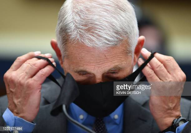 Director of the National Institute for Allergy and Infectious Diseases Dr. Anthony Fauci takes off his face before he testifies before the US Senate...
