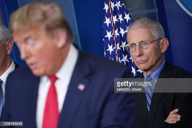 Director of the National Institute of Allergy and Infectious Diseases Anthony Fauci listens as US President Donald Trump speaks during the daily...