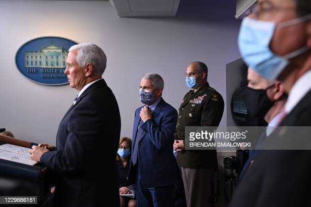 Director of the National Institute of Allergy and Infectious Diseases Anthony Fauci listens to Vice President Mike Pence speak during a White House...