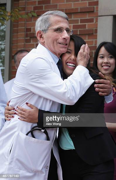 Director of the National Institute of Allergy and Infectious Diseases Anthony Fauci hugs Nina Pham the nurse who was infected with Ebola from...