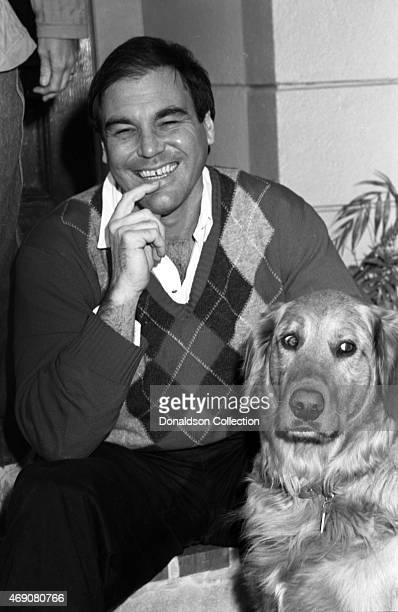 Director Oliver Stone and his dog poses for a portrait session at home in circa 1986 in Los Angeles California