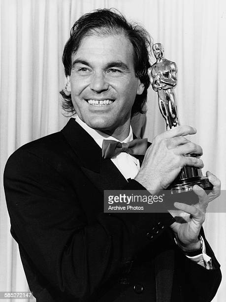 Director Oliver Stone holding his Oscar statuette at the 62nd Academy Awards Los Angeles March 26th 1990