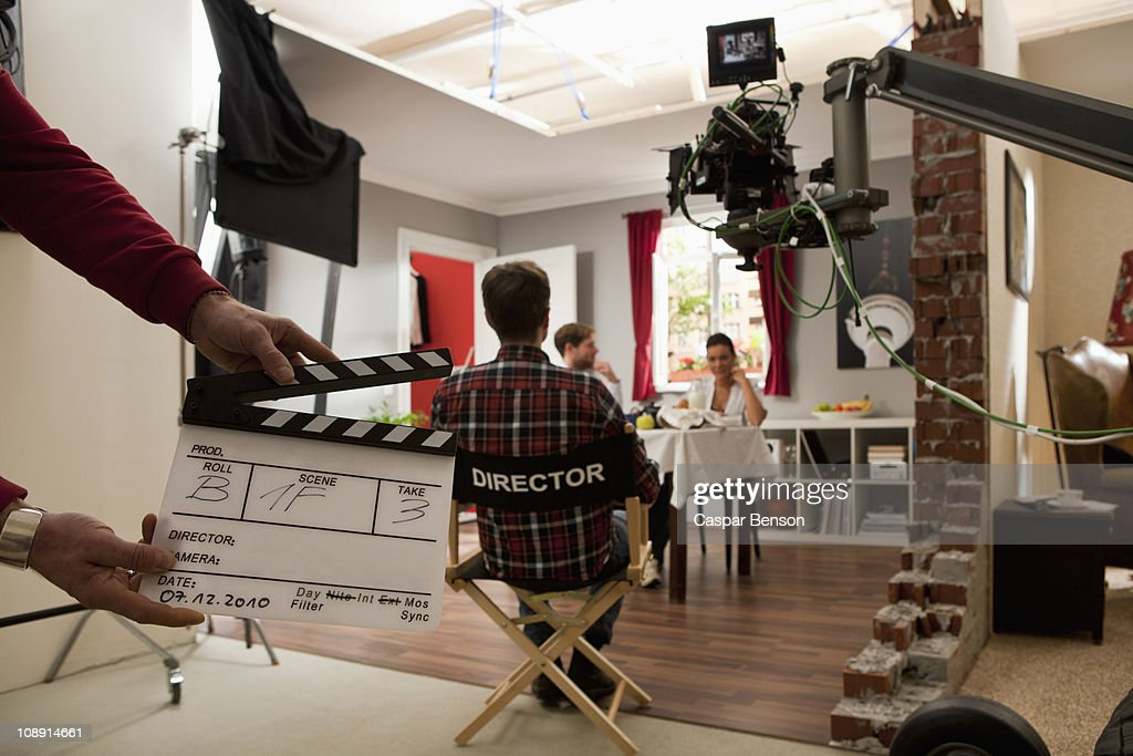 A director on a film set watching actors perform a scene : Stock Photo