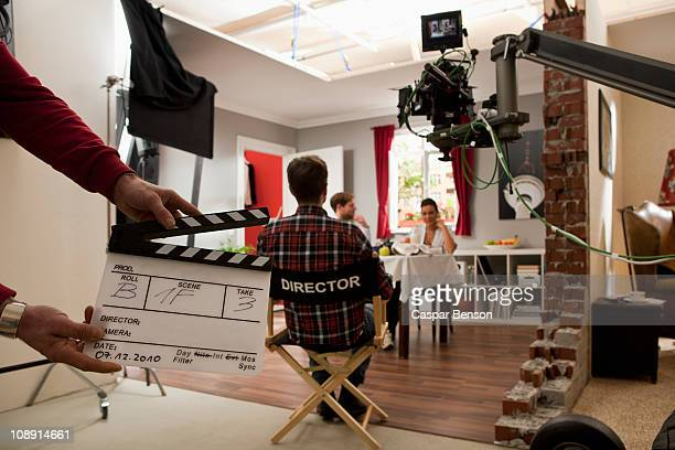 a director on a film set watching actors perform a scene - filmen stockfoto's en -beelden