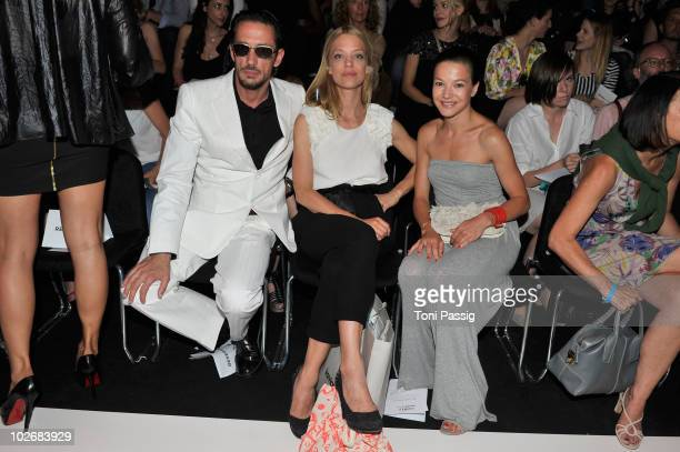 Director Oskar Roehler actresses Heike Makatsch and Hannah Herzsprung pose in front row at the Kaviar Gauche Show during the Mercedes Benz Fashion...