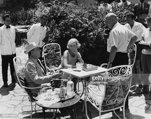 Director Otto Preminger talking to actors Sir Ralph Richardson and Eve Marie Saint as they relax at an outdoor table on the set of the film 'Exodus'...