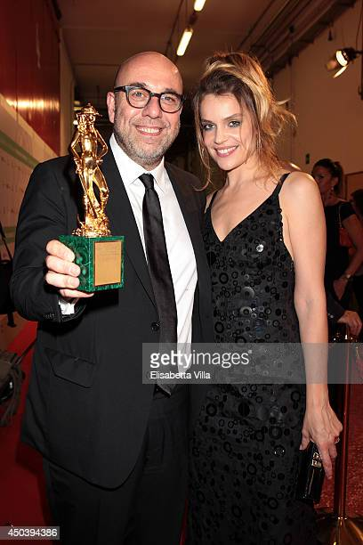 Director Paolo Virzi and Micaela Ramazzotti pose with the best film award for 'Il Capitale Umano' as he attends the David Di Donatello Awards...