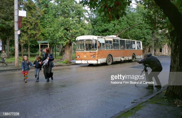 Director Paul Cowan films a woman and two chidren as they cross a street with a tram car on his right in Sukhumi capital of Abkhazia November 2002...