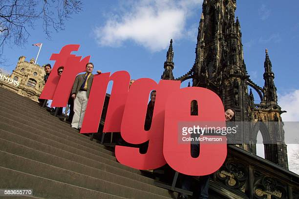 Director Paul Gudgin of the Edinburgh Festival Fringe stands in as the letter 'i' at the launch of the new logo on Princes Street.