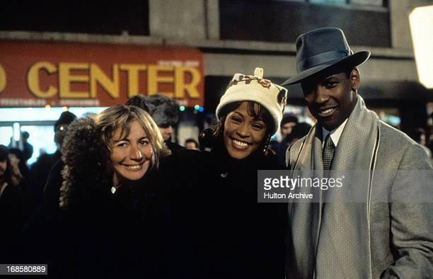 Director Penny Marshall smiles with Whitney Houston and Denzel Washington at the premiere of the film 'The Preacher's Wife' 1996
