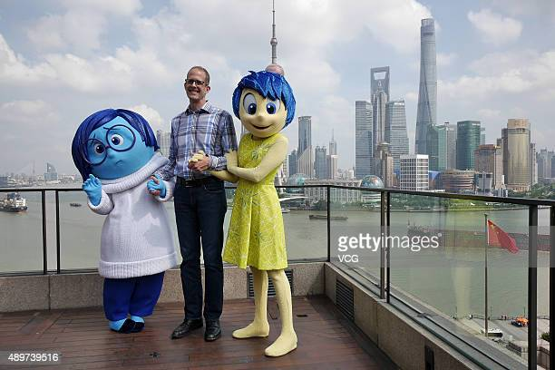 Director Pete Docter poses with cartoon roles during the press conference of his film 'Inside Out' at The Bund on September 24 2015 in Shanghai China