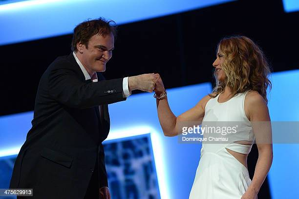 Director Quentin Tarantino bumps mistress of ceremonies actress Cecile de France on stage during the 39th Cesar Film Awards 2014 at Theatre du...