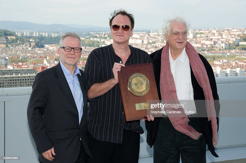 US Director Quentin Tarantino poses with the Lumiere Award next to Thierry Fremaux (L) and director Bertrand Tavernier, in front of a general view of the City of Lyon, during the 5th Lumiere Film Festival, in Lyon.