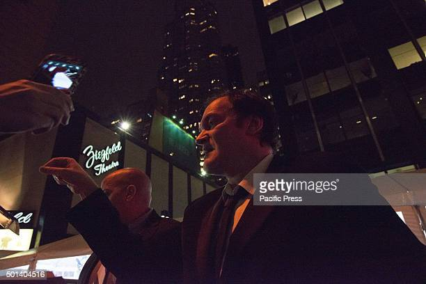 Director Quentin Tarantino signs autographs for activists gathered opposite the theater upon his arrival at the premiere of 'Hateful Eight' At the...