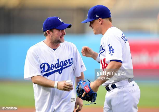 Director Rian Johnson shakes hands with Enrique Hernandez of the Los Angeles Dodgers after throwing out a ceremonial first pitch before the game...