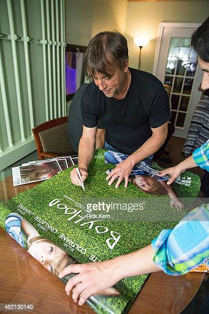 Director Richard Linklater signs a movie poster during the premiere of 'Boyhood' at Marchesa Hall & Theater on July 13, 2014 in Austin, Texas.