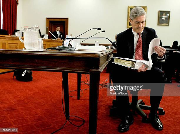 Director Robert S. Mueller looks over his papers before testifying to a House Commerce, Justice, State and Judiciary subcommittee on Capitol Hill...