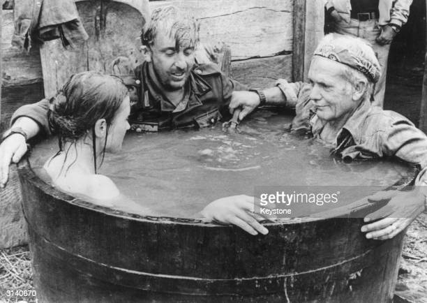 Director Sam Peckinpah joins German actor Vadim Glowna and a Yugoslav actress in the tub during a rehearsal for his wartime drama 'Cross Of Iron'