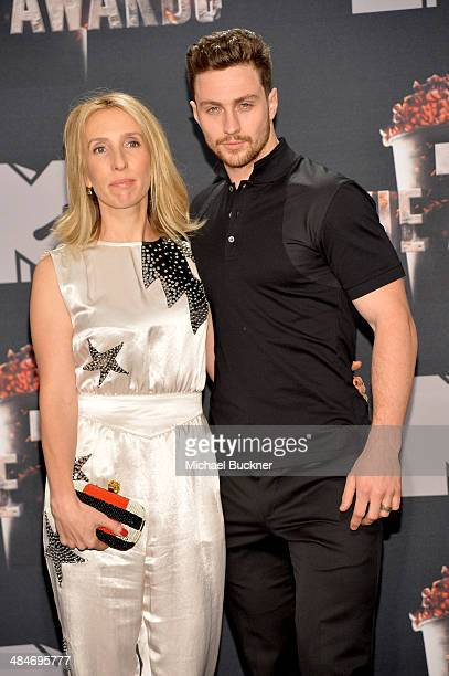 Director Sam TaylorWood and actor Aaron TaylorJohnson pose in the press room during the 2014 MTV Movie Awards at Nokia Theatre LA Live on April 13...