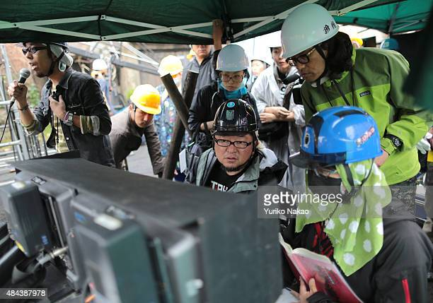 Director Shinji Higuchi checks shots with his crew between takes during the filming of 'Attack on Titan' on June 9 2014 in Takahagi Japan