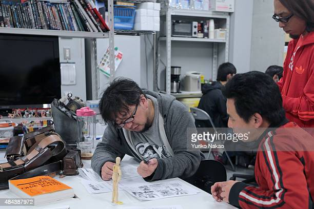 Director Shinji Higuchi looks at his storyboard as he speaks with his crew for 'Attack on Titan' at a working room in Toho Studios on April 4 2014 in...