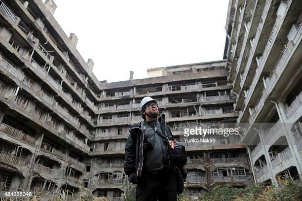 Director Shinji Higuchi poses in front of an abandoned building during a location hunting for his film 'Attack on Titan' on Hashima Island commonly...