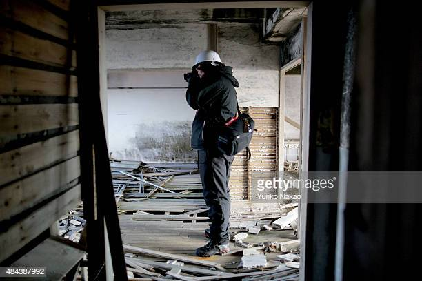 Director Shinji Higuchi takes photograph inside an abandoned building during a location hunting for his film 'Attack on Titan' on Hashima Island...