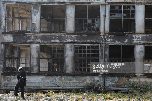 NAGASAKI JAPAN DECEMBER Director Shinji Higuchi walks in front of an abandoned building during a location hunting for his film 'Attack on Titan' on...