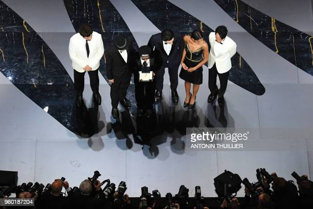 US director Spike Lee poses on stage after he was awarded with the Grand Prix for the film 'BlacKkKlansman' as USPuerto Rican actor and President of...
