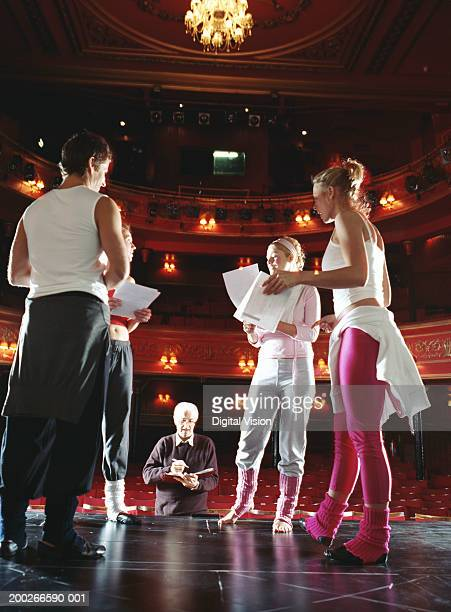 Director standing by group of people rehearsing on stage