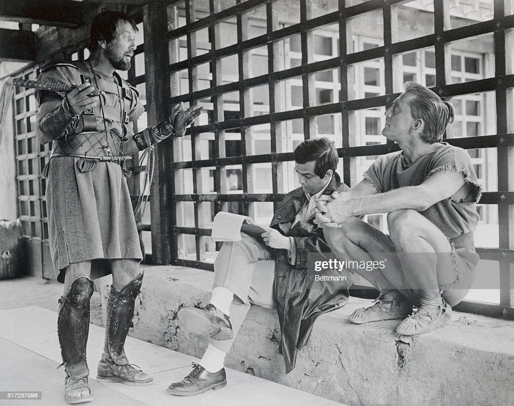 Director Stanley Kubrick makes notes on his script while Charles McGraw (L) and Kirk Douglas (R) discuss a forthcoming scene for the 1960 film Spartacus.