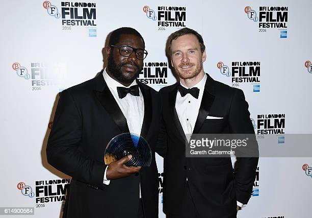 Director Steve McQueen with his BFI Fellowship award with award presenter Michael Fassbender attends the BFI London Film Festival awards during the...