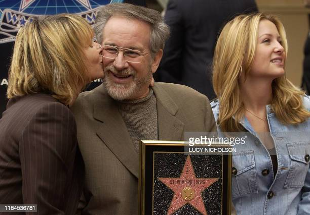 Director Steven Spielberg is kissed by his wife actress Kate Capshaw as he poses with their daughter Jessica Capshaw after a star was unveiled for...