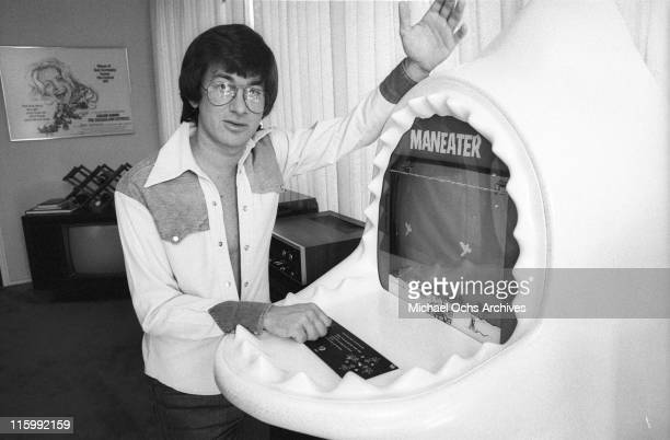 Director Steven Spielberg poses for a photo with a 'Maneater' arcade game at his Universal studios office in December 1975 in Los Angeles California
