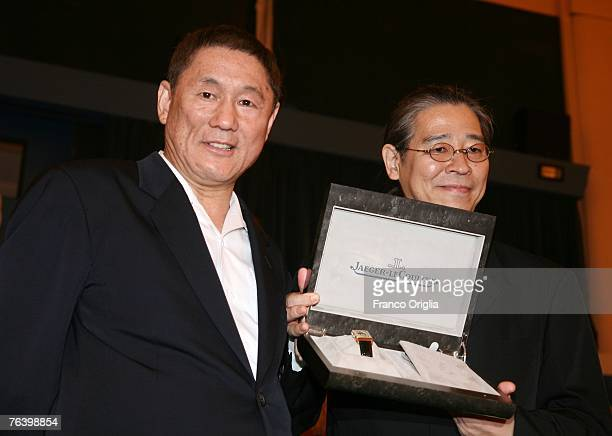 Director Takeshi Kitano and producer Masayuki Mori pose with the JaegerLe Coultre Award during the Kantoku Banzai premiere on Day 2 of the 64th...