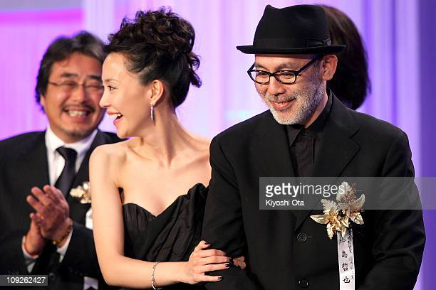 Director Tetsuya Nakashima accepts the Best Picture award for 'Kokuhaku' on stage beside actress Yoshino Kimura during the 34th Japan Academy Awards...