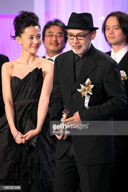 Director Tetsuya Nakashima holds a trophy on stage beside actress Yoshino Kimura as he accepts the Best Picture award for 'Kokuhaku' during the 34th...
