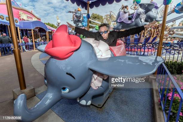 Director Tim Burton poses with Dumbo the Flying Elephant at Disneyland during a sneak peek of the upcoming liveaction adventure Dumbo on March 9 2019...