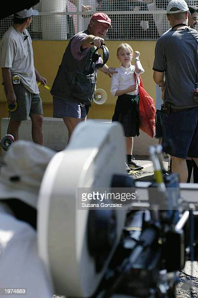 Director Tony Scott directs actress Dakota Fanning while filming a scene of Man On Fire at a sports club May 5 2003 in Mexico City Mexico