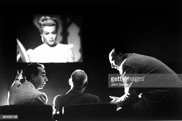 Director Vincente Minnelli with producer John Houseman and unidentified, discussing their film The Bad and the Beautiful with Lana Turner, during...