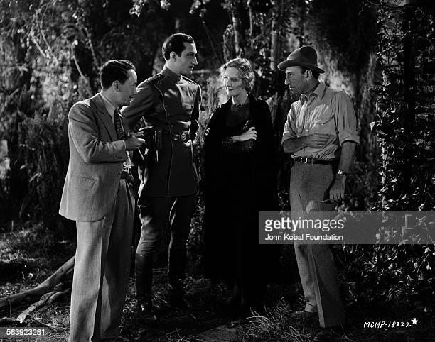 Director William C DeMille talking to actors Basil Rathbone and Kay Johnson on the set of the film 'This Mad World' for MGM Studios July 13th 1929