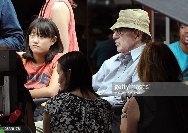 US director Woody Allen flanked by one of his adopted children Manzie Tio is pictured in a street of Paris on July 27 2010 during the shooting of his...
